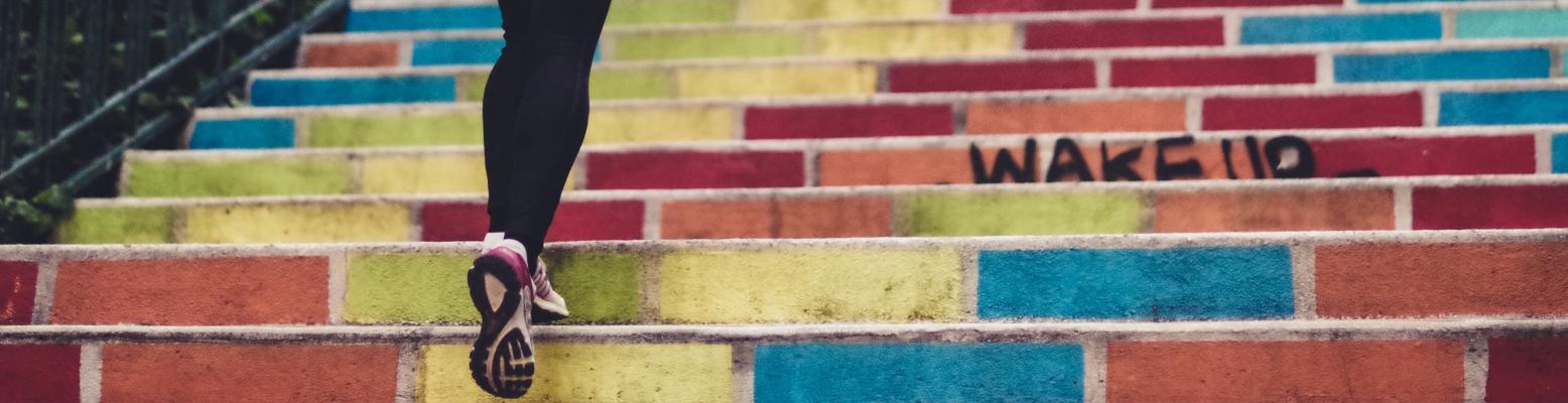 Person med löparskor springer upp för en trappa med många färger