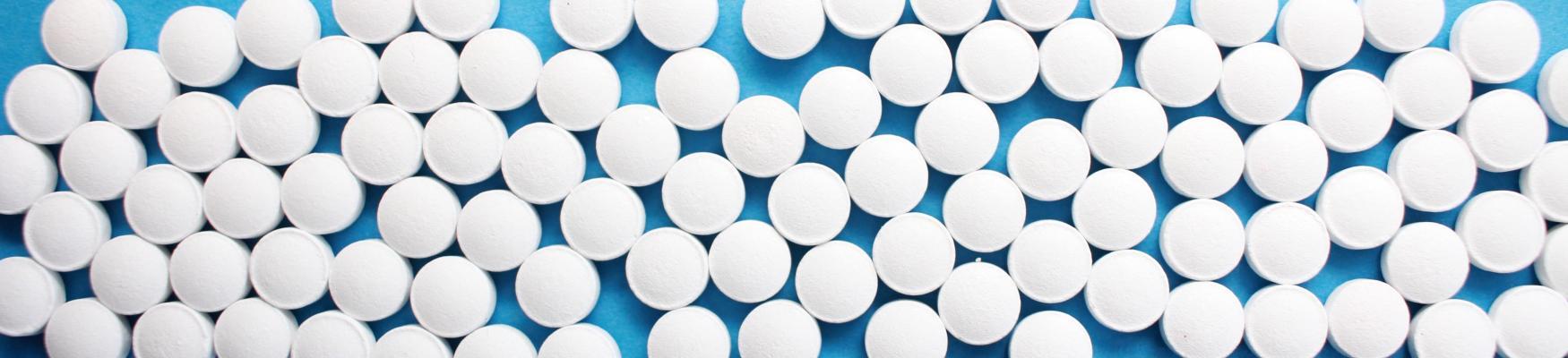 Många vita piller på ett bord